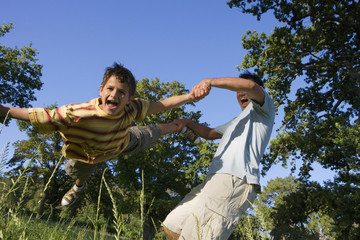 Father swinging son (9-11) in woodland clearing, boy shouting, low angle view (tilt)