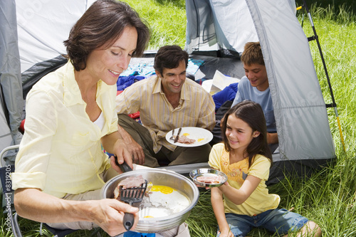 Family eating fried breakfast on camping trip, woman serving bacon to daughter (8-10) beside tent