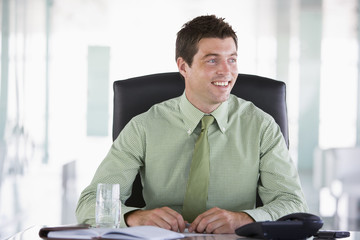 Businessman sitting in office with personal organizer smiling
