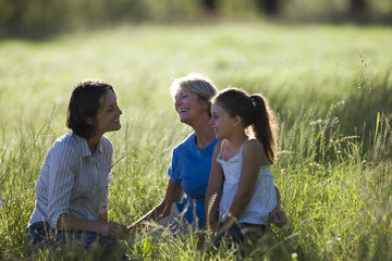 Girl (7-9) sitting with mother and grandmother in field, smiling, side view