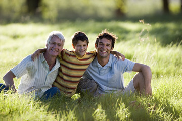 Boy (8-10) sitting with arms around father and grandfather in field, smiling, front view, portrait