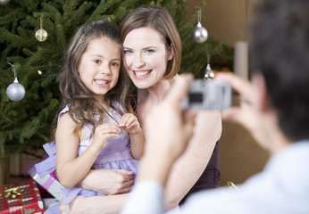A father taking a photo of his family at Christmas