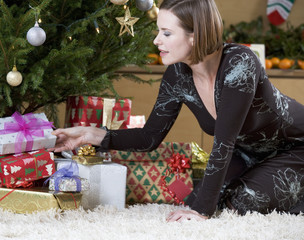 A woman putting presents under the Christmas tree