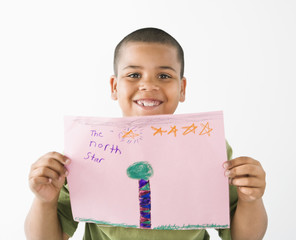 Smiling hispanic boy holding drawing.