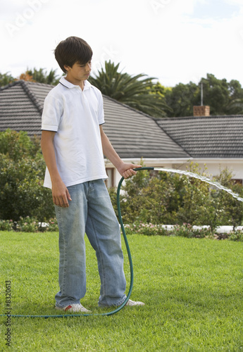 A young boy watering the garden with a hose