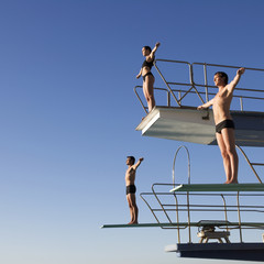 Three divers standing on diving boards