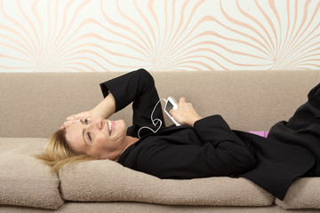 Woman in suit laying on sofa listening to music