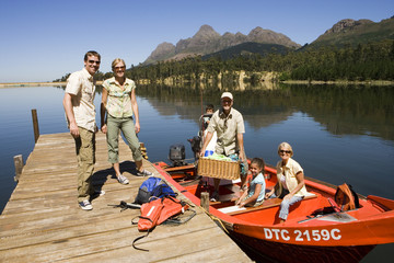 Multi-generational family loading motorboat with provisions on lake jetty, smiling, portrait