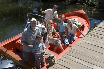 Multi-generational family standing in motorboat moored at lake jetty, smiling, portrait
