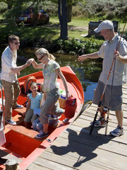 Multi-generational family boarding motorboat on lake jetty, man offering wife helping hand, senior man with fishing rod