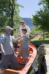 Boy (8-10) boarding motorboat moored at lake jetty, father and grandfather assisting, side view