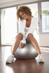A young woman sitting on an exercise ball