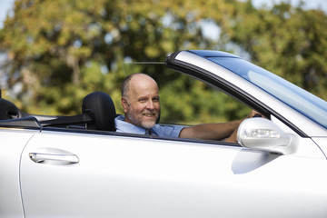 A senior man driving a car
