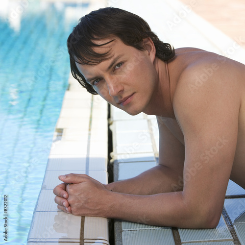 A young man laying by a swimming pool