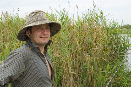 smiling fisher in a reed