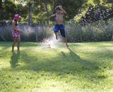 Young boy and girl playing with water in the garden