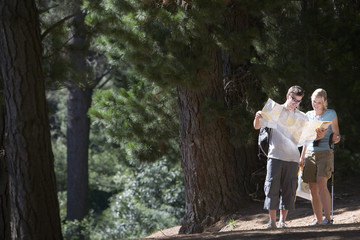 Young couple, with rucksacks, hiking along woodland trail, consulting map, woman holding hiking pole, smiling