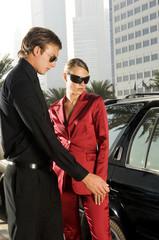 A wealthy couple unlocking their car