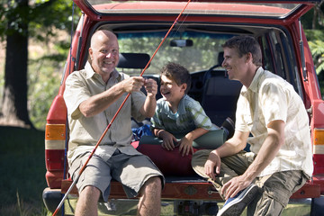 Boy (8-10) sitting in boot of parked SUV with father and grandfather, senior man holding fishing rod, smiling
