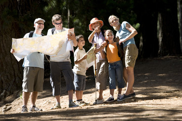 Multi-generational family hiking along woodland trail, men looking at map, senior woman pointing