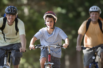 Boy (8-10), in cycling helmet, mountain biking on woodland trail with father and grandfather, front view