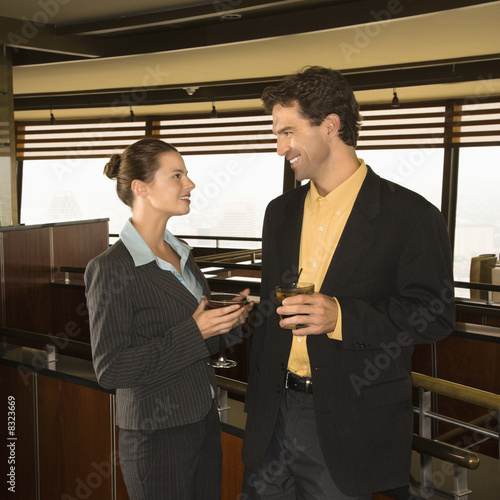 Man and woman drinking at bar.