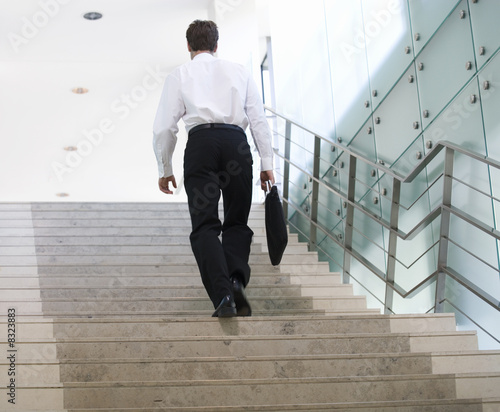 A businessman walking up stairs
