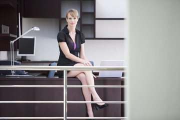 A businesswoman sitting on a desk