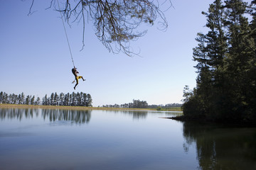 Boy (8-10), in mid-distance, swinging on rope above lake, side view