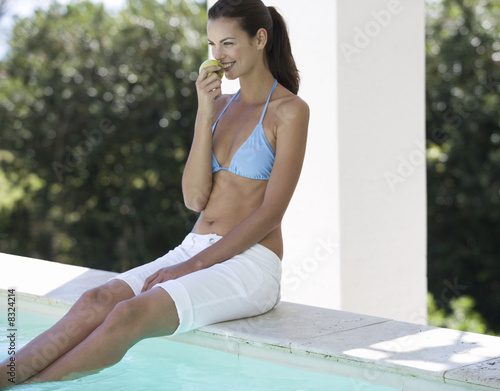 A woman sitting on the edge of a swimming pool eating an apple
