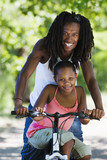 Father and daughter (7-9) sitting on mountain bike, smiling, portrait