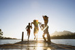 Family, in swimwear, running along jetty, jumping into lake at sunset, rear view (surface level, lens flare)
