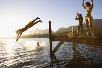 Father and son (8-10), in swimwear, diving off jetty into lake at sunset, mother and daughter (7-9) cheering (lens flare)