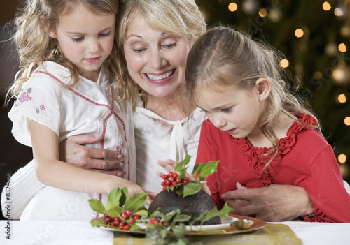 A grandmother and her granddaughters looking at a Christmas pudding