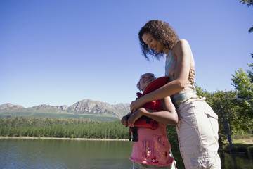 Mother helping daughter (7-9) put on life jacket, standing on lake jetty, smiling, side view