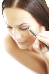 Young woman applying make-up, close-up