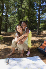 Mother and daughter (7-9) resting on lakeside woodland trail beside map and compass, girl embracing woman, smiling, portrait