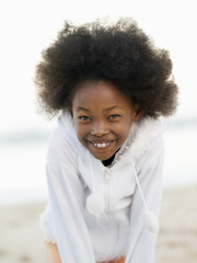 Girl (7-9), with afro, wearing white top, smiling, close-up, portrait