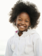 Girl (7-9), with afro, wearing white top, smiling, close-up, front view, portrait