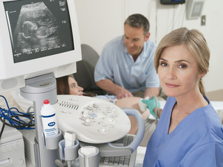 Pregnant woman having ultrasound scan in hospital, husband holding hand, focus on female doctor in foreground, portrait
