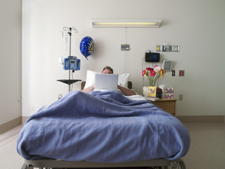 Male patient lying in hospital bed, using laptop, face obscured, front view