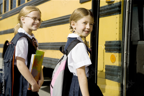 Two schoolgirls getting on a school bus
