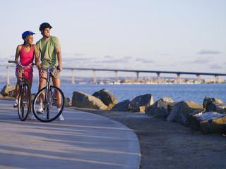 USA, California, San Diego, couple cycling near Coronado Bay Bridge, looking at scenery, smiling