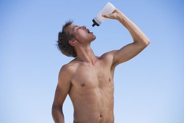 A young man drinking from a water bottle after exercising