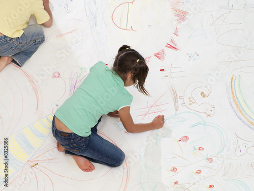 Boy and girl (7-10) drawing on large piece of paper laid out on living room floor, overhead view