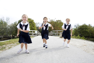Three schoolgirls running down a road