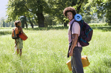 Young couple, with rucksacks, standing in woodland clearing, departing on hiking trip, side view, smiling, portrait