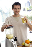 Young man preparing fresh fruit juice