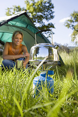 Young woman sitting inside dome tent in woodland clearing, waiting for kettle to boil on camping stove, smiling (surface level)