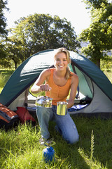 Young woman kneeling beside dome tent in woodland clearing, taking boiled kettle from camping stove, smiling, portrait